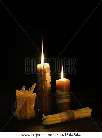 Antique candles burning in the darkness, vertical image with copy space