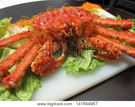 Fried red king crab with lettuce on white plate in restaurant
