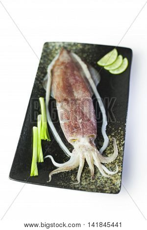 Fresh squid with onion and lemon on black plate on white background