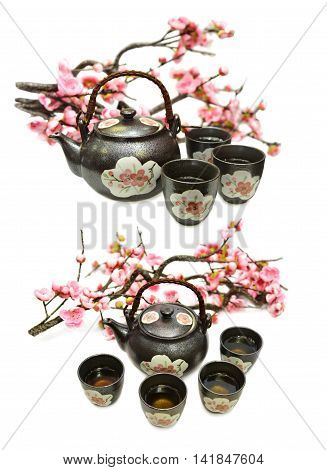 Set with black ceramic tea pot, cups and sakura branch, isolated objects, japanese tea ceremony