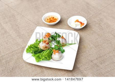 Vietnamese glutinous rice cake or Ram It Hue on white plate with lettuce and herbs