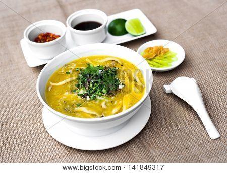 Vietnamese clams porridge in white bowl with lemon and chili sauce