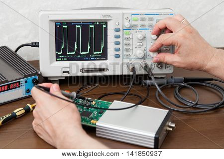 Engineer's hands measuring signals on board of the electronic device