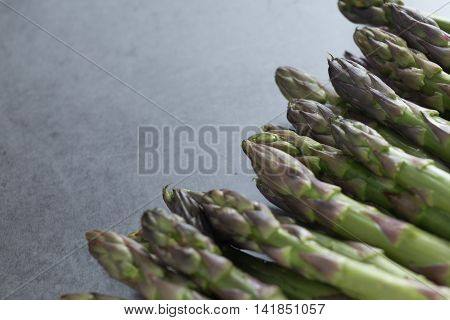 Bunch of asparagus on a table. Uncooked pile raw for organic, vegetarian cuisine, delicious fresh, healthy ingredient. Closeup and copy space.