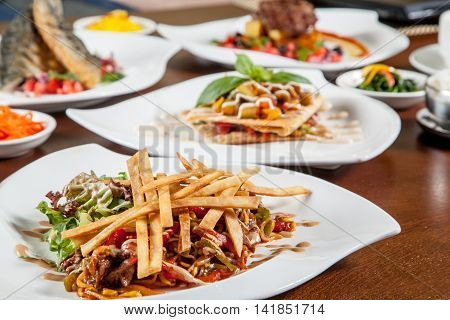 Korean beef salad with fried potatoes on white plate