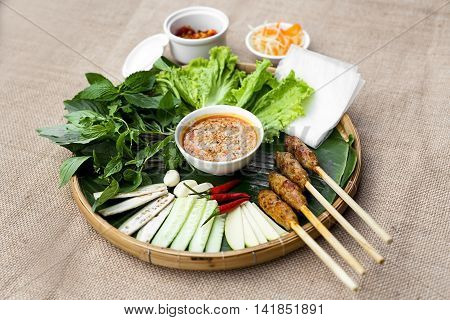 Vietnamese fermented pork roll or nem Hue with lettuce herbs and chili sauce on bamboo tray Vietnamese fermented pork roll