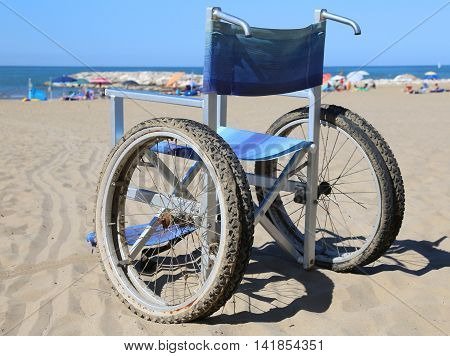 Wheelchair On The Beach Sand Near The Sea