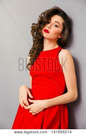 Portrait of a young attractive woman in red dress standing over gray bakground