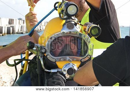 Photo of a diver who is willing to dive - he is dressed in a suit and helmet
