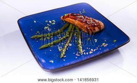 Salmon teriyaki with asparagus in blue chinese plate on white background