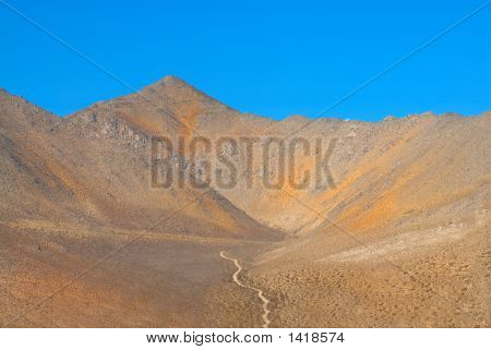 Lone Dirt Road In The Mountains Of Death Valley