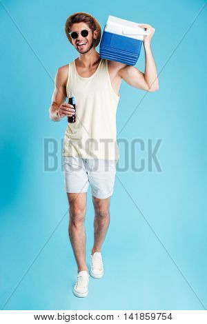 Smiling young man with cooling bag on his shoulder walking and drinking soda over blue background