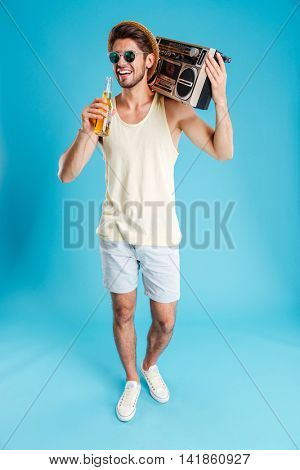 Cheerful young man in hat and sunglasses with boombox walking and drinking beer over blue background