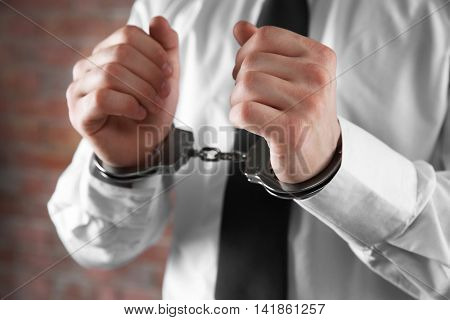 Man in handcuffs on brick wall background