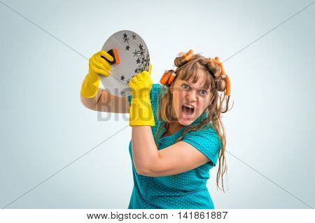 Aggressive housewife woman with yellow rubber gloves washing dishes on blue background