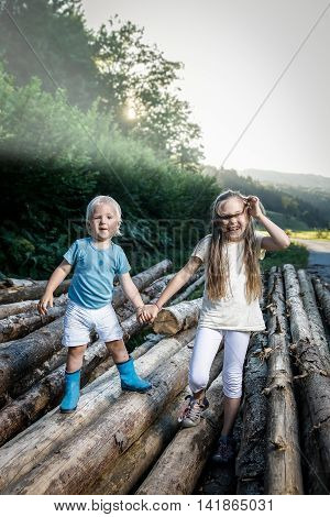 Brother and sister holding hands enjoying their time together walking in nature climbing logs. Happy carefree outdoor countryside childhood siblings love family values concept.