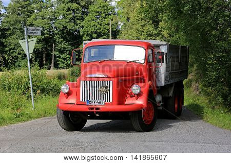 TENHOLA FINLAND - JULY 30 2016: Classic red Volvo N86 tipper truck enters main road on a beautiful day of summer in South of Finland.