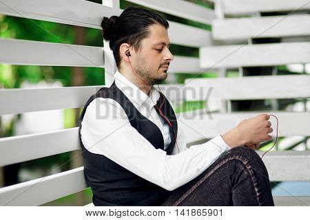 Attractive hipster man using a smartphone and listening music. Handsome male relaxing on steps.