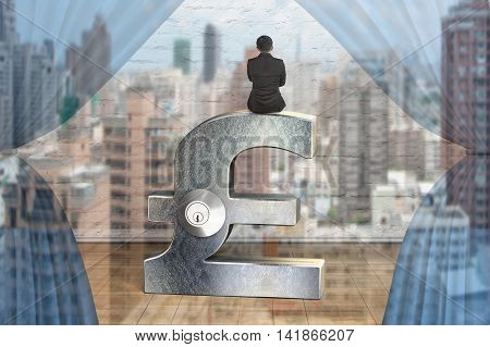 Businessman Sitting On Silver Pound Symbol With Lock