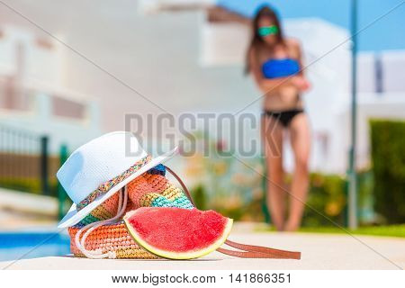 Colorful stripe bag, slice of watermelon, orange juice, and straw white hat on summer vacation near pool background young woman