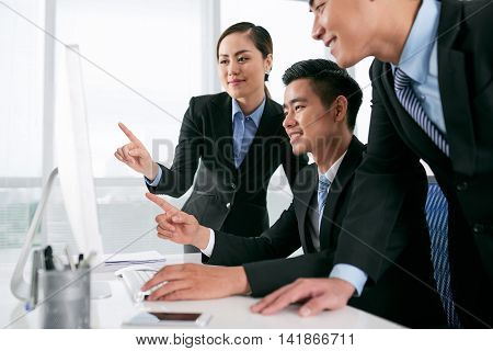 Asian business team gathered in front of computer screen