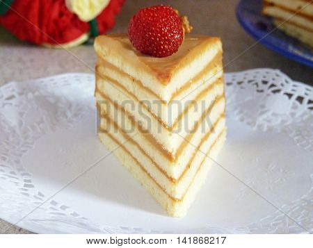 Piece of Layered Sponge Cake Decorated with Strawberry and Walnut