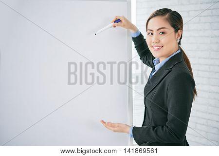 Pretty business lady explaining ideas on whiteboard