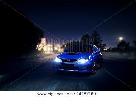 Moscow, Russia - June 18, 2016: Blue car Subaru Impreza WRX STI stay on asphalt countryside road near city and forest at moon night