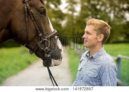 man and his brown horse at a farm
