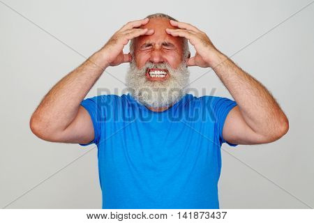 Bearded man is clenching his teeth and pressing his head with fingers while having a migraine against white background