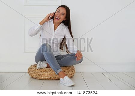 A cheerful young woman is full of happiness while hearing great news. She is wearing denim light-gray skinny jeans and a white fitted blouse while sitting on a hassock