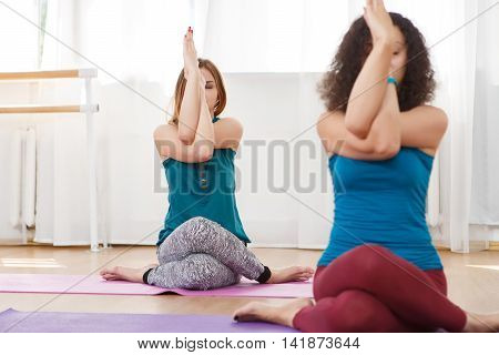 Portrait of two young caucasian barefoot woman sitting doing yoga exercise in light gym