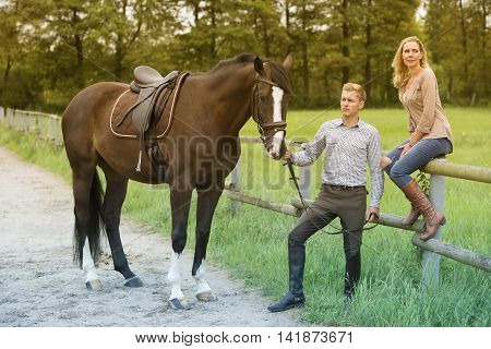 man and woman with horse at a fram