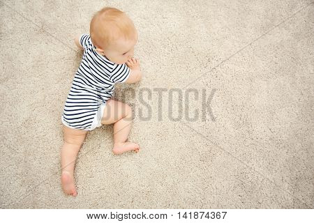 Adorable little baby crawling on light carpet