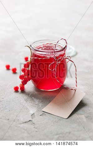 Homemade red currant jam or syrup on a stone background. Closeup.