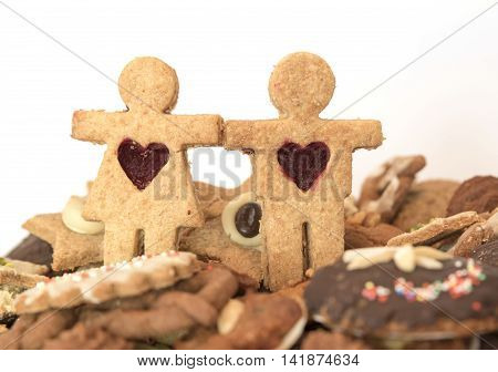 Christmas cookie couple against plate with handmade wholemeal cookies. Selected focus.