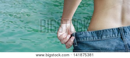 Back or rare of women undress denim jeans on sea or crystalline water surface background with blank space area