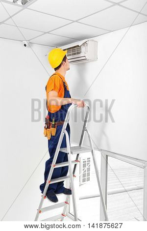 Technician repairing air conditioner on the wall