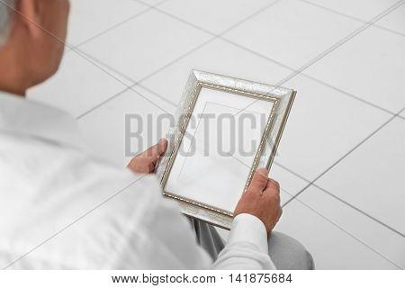 Man holding photo frame. Memories and nostalgia concept