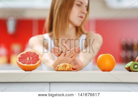 Woman refuse eating croissant lying among fruits