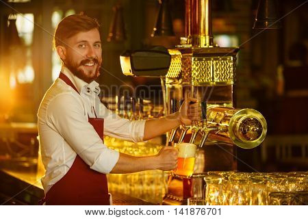 Young waiter pours a beer in a bar