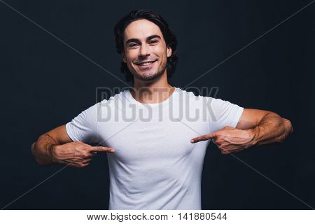 Copy space on his T-shirt. Portrait of cheerful young man looking at camera and pointing copy space on his T-shirt while standing against grey background