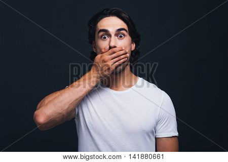 Oh no! Surprised young man covering mouth with hand and staring at camera while standing against grey background