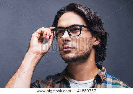 Lost in thoughts. Thoughtful young man adjusting his eyeglasses and looking away while standing against grey background