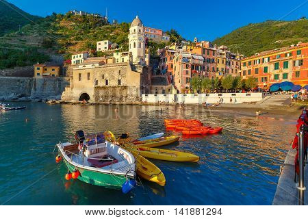 The colorful fishing boats and Santa Margherita di Antiochia Church in Vernazza harbour in Five lands, Cinque Terre National Park, Liguria, Italy.