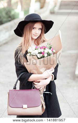 Smiling teen girl 14-16 year old wearing winter jacket and hat holding stylish bag and roses wrapped in craft paper outdoors. Looking at camera. Beautiful girl posing.
