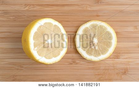 Top view of a cut lemon with a slice to the side atop a wood cutting board.