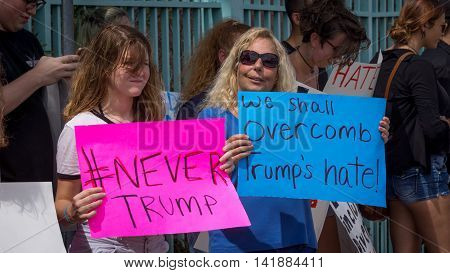Daytona Beach, FL - August 3, 2016: Two protestors at a Donald Trump rally hold up their signs as other protestors look on in Daytona Beach, FL.