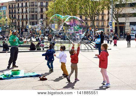 Barcelona Spain - April 3 2016: Children catching the soap bubbles in the Catalonia Square (Plaza de Cataluna) is a large square in central Barcelona. Spain