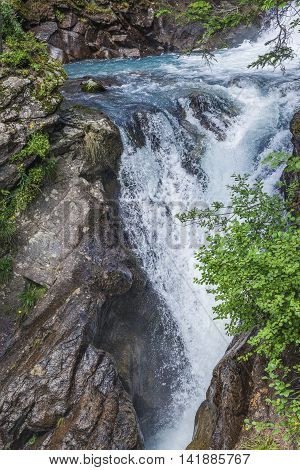 Alpine Waterfall In Mountain Forest